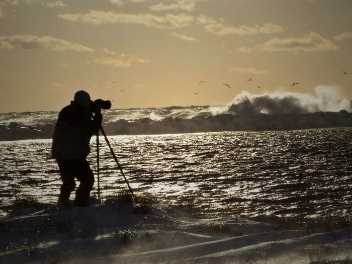 Silhouette man photographing at beach against sky during sunset