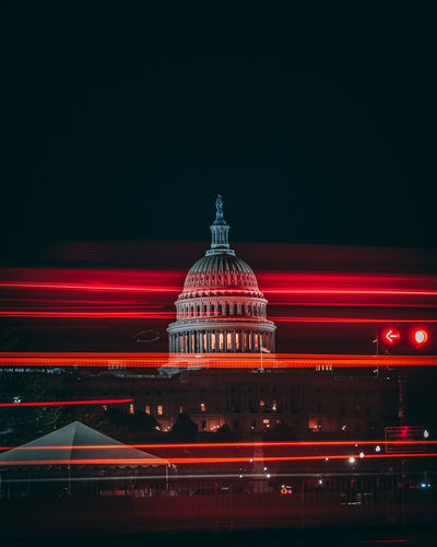 Red light trails against government building at night
