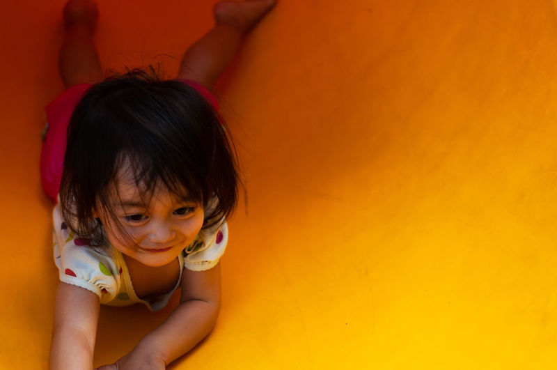 High angle view of cute girl lying on yellow slide