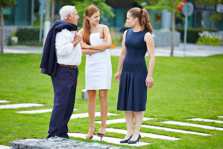 Business People Discussing While Standing On Grassy Field