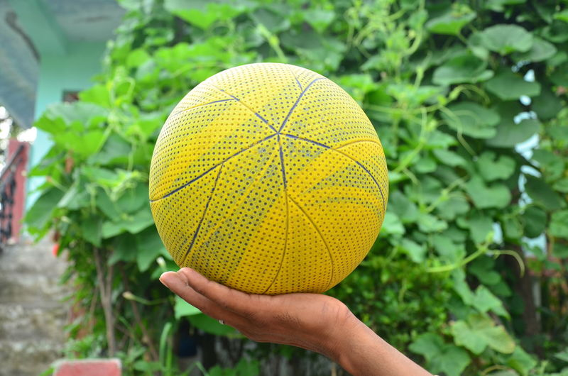 Close-up of hand holding yellow ball