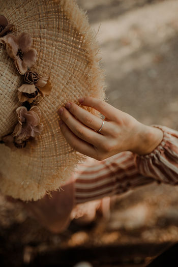 Close-up of woman holding hat