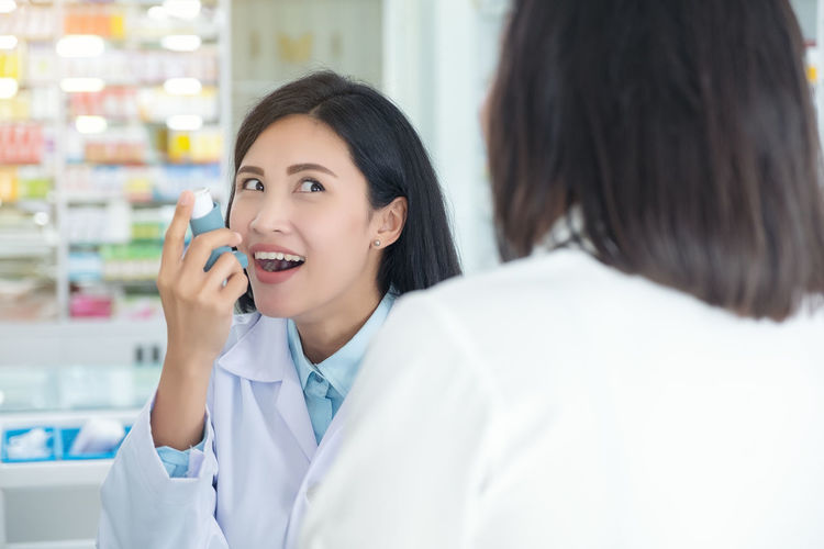 Doctor test and teach spray and checking for a patient's mouth Smiling Adult Women Happiness Indoors  Young Adult Beauty Healthcare And Medicine Females Young Women Headshot Make-up Beautiful Woman Holding Communication Portrait People Emotion Occupation Talking Lab Coat