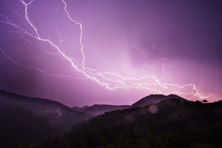 Scenic view of lightning over mountains