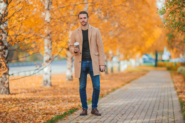 Full length of young man using smart phone during autumn