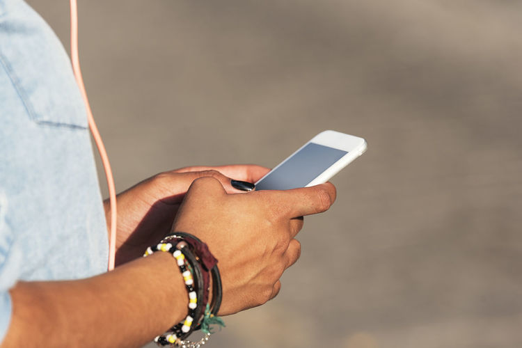 Midsection Of Woman Using Mobile Phone Outdoors