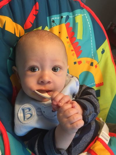 Portrait of cute baby boy carrying spoon in mouth