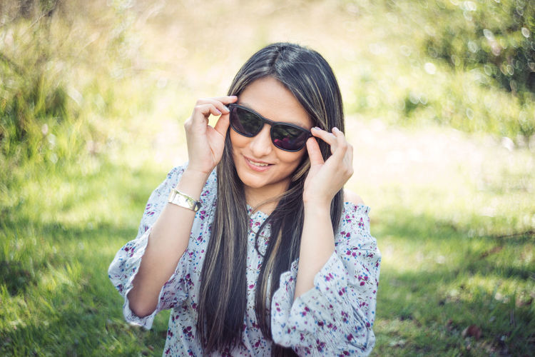 Portrait of smiling young woman wearing sunglasses standing outdoors