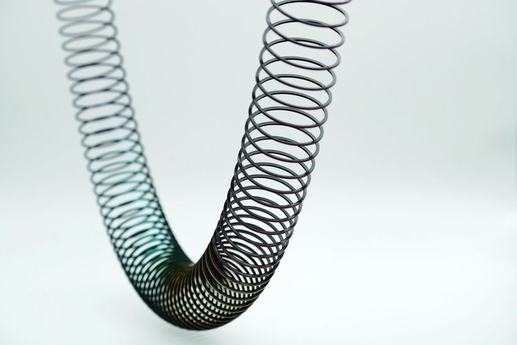 Close-up of coiled spring against white background