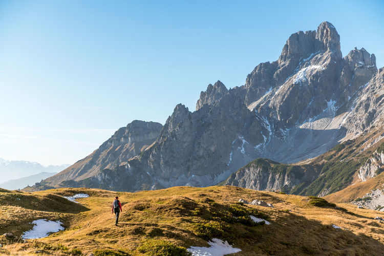 Woman hiking on footpath in alpine landscape, bischofsmütze, filzmoos, austria