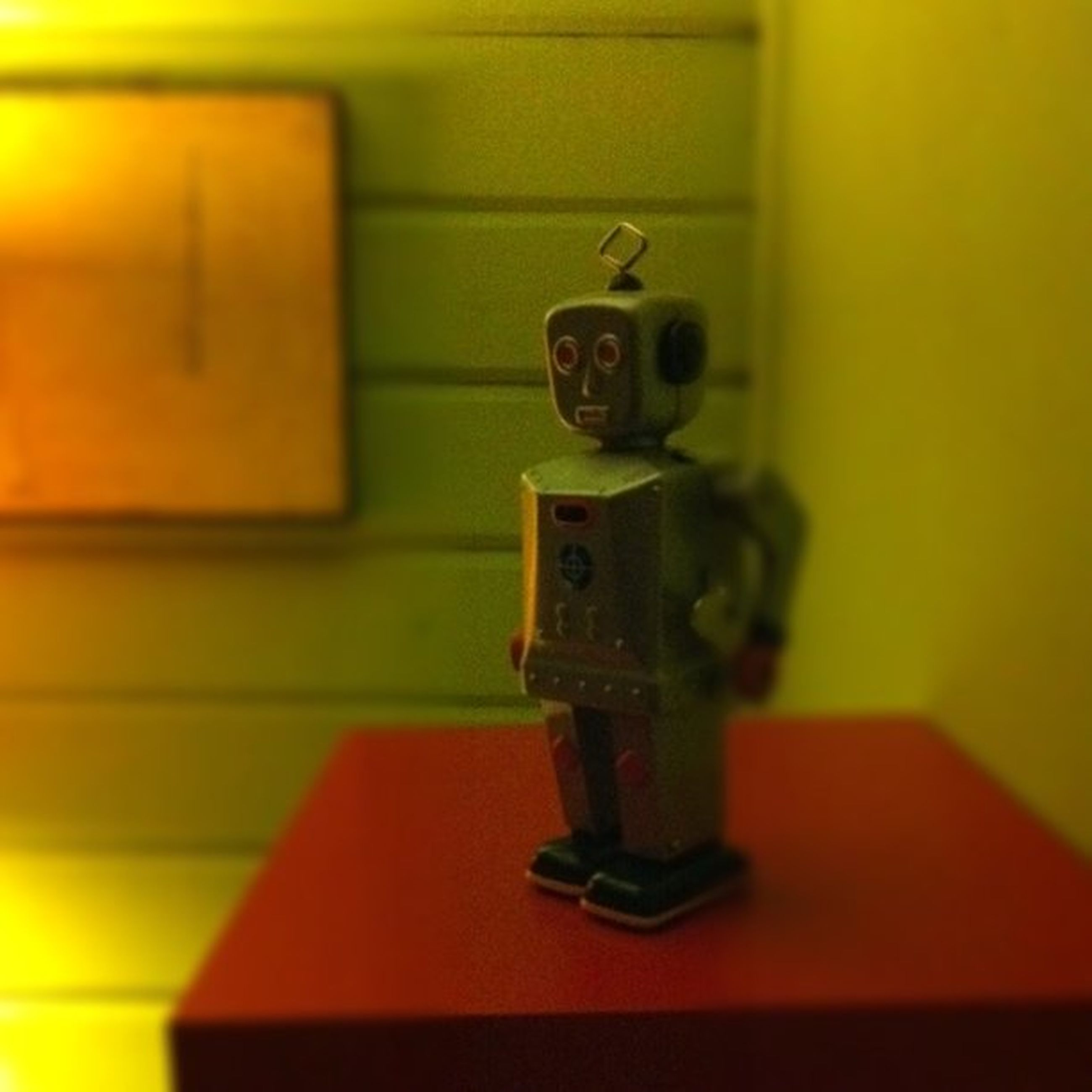 indoors, human representation, wall - building feature, art and craft, home interior, art, door, creativity, close-up, selective focus, wall, built structure, no people, focus on foreground, architecture, yellow, toy, house, figurine