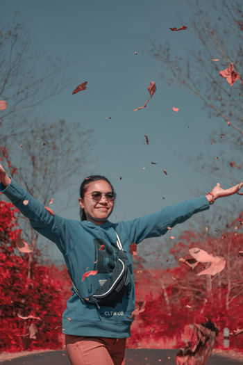Portrait of smiling young woman throwing gray leaves