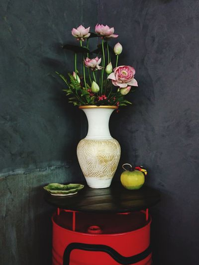 Close-up of white roses in vase on table against wall