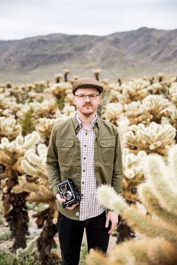 Portrait of man wearing hat standing on land
