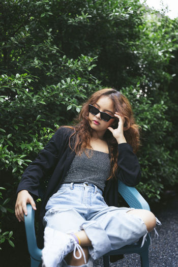 Young woman sitting on sunglasses against trees