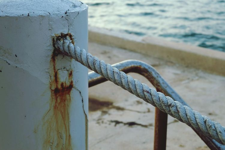 Close-Up Of Rope By Pole At Beach