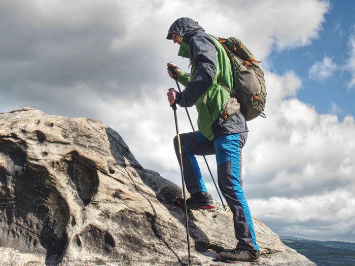 Man backpacker climbing over sandstone bolder high up on a mountain hike