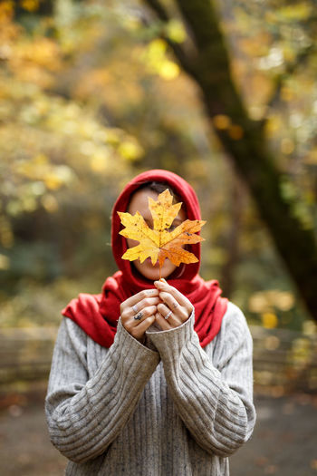 Woman covering face with autumn leaf