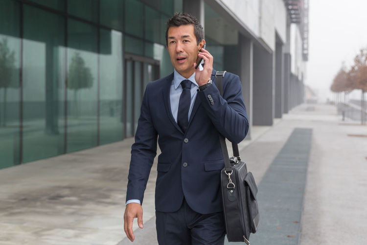 Businessman walking against building