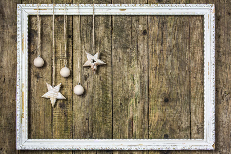 Christmas Decorations Hanging From Picture Frame Mounted On Wooden Wall