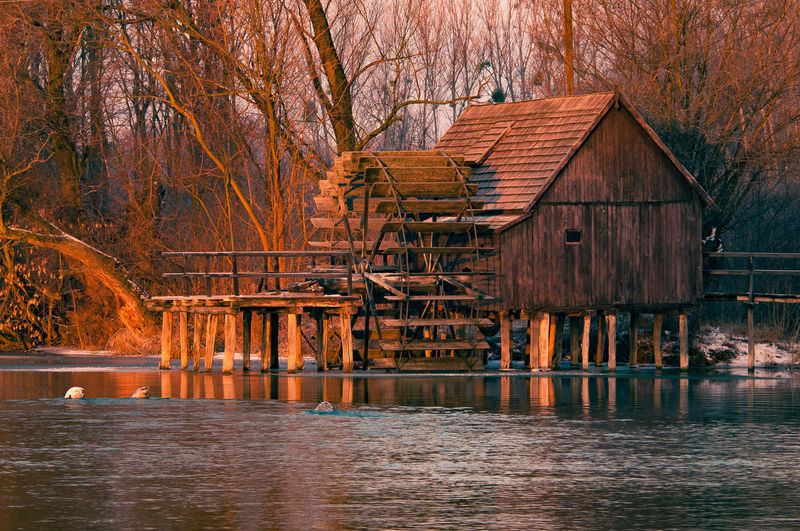 Waterwheel by stilt house on lake