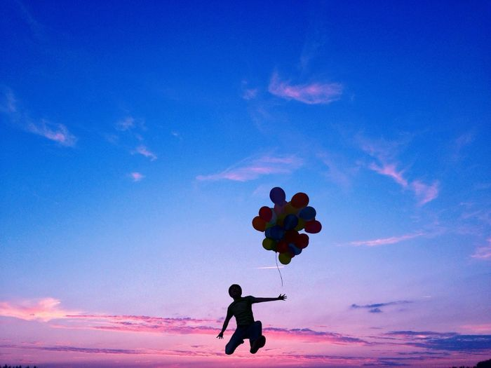 Person jumping with balloons at sunset