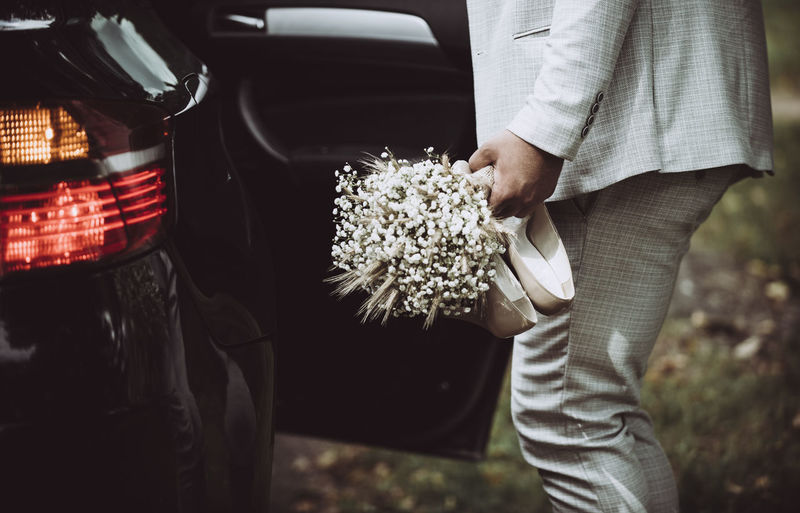 Midsection of man holding bouquet by car