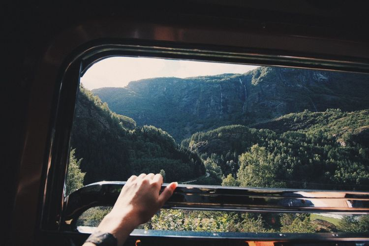 Cropped hand of woman holding window railing against mountain in bus