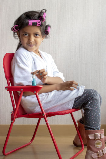 Portrait Of Girl Applying Nail Polish While Sitting On Chair At Home