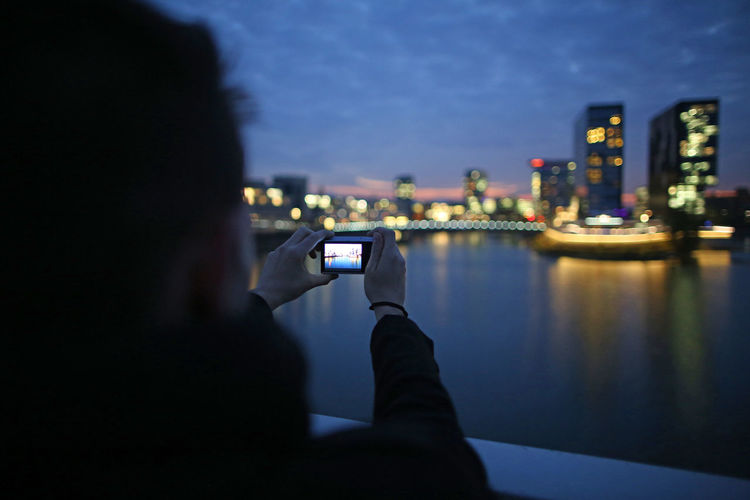 Woman Photographing Illuminated Skyscrapers By River From Camera