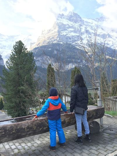 Real People Rear View Full Length Two People Leisure Activity Day Lifestyles Standing Nature Mountain Sky Tree Grindelwald Casual Clothing Togetherness Beauty In Nature Switzerland Outdoors Childhood The Great Outdoors - 2017 EyeEm Awards Live For The Story Let's Go. Together. Lost In The Landscape