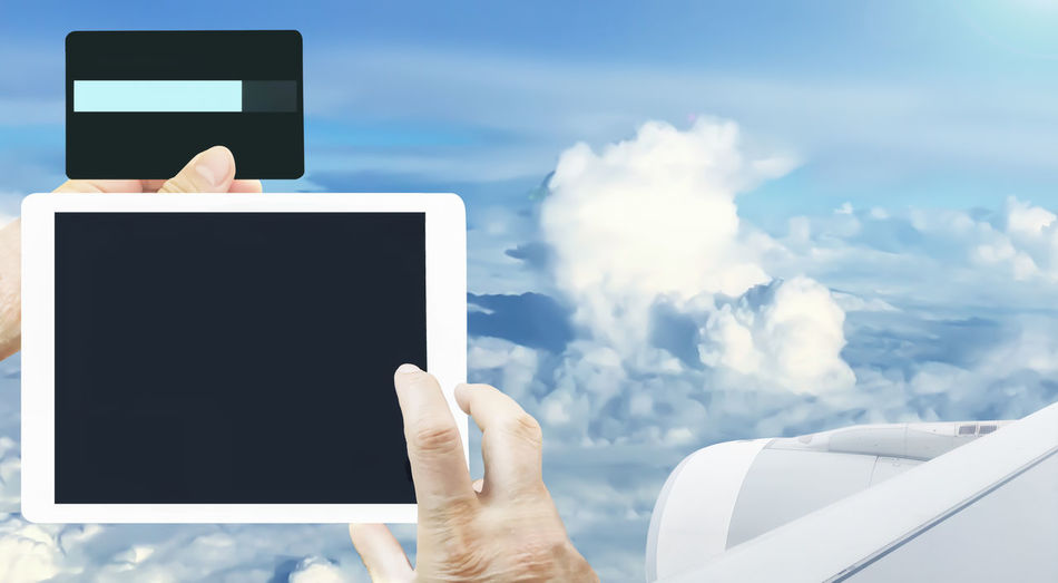 Cropped Hands Using Digital Tablet With Airplane Flying In Background Against Cloudy Sky
