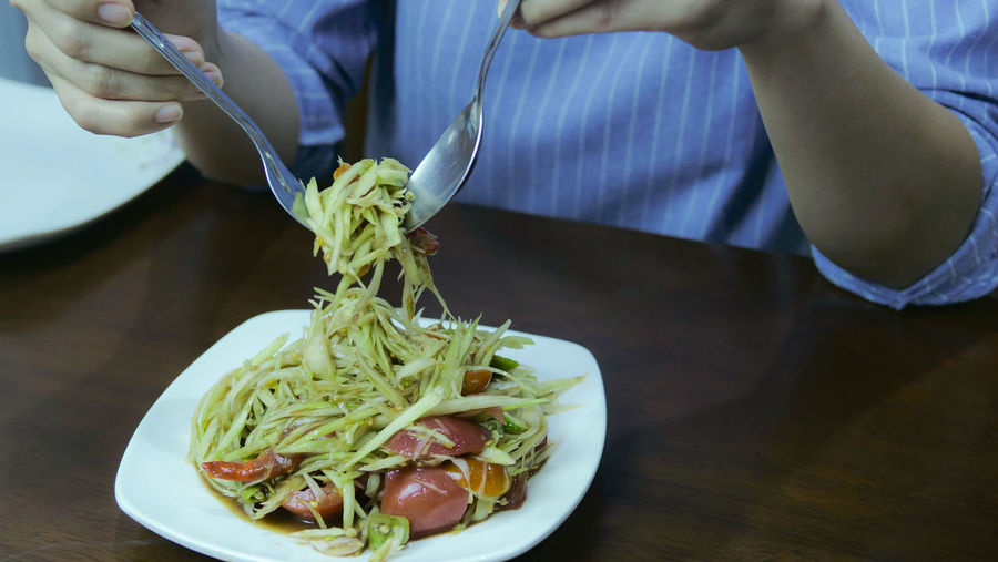 Midsection of woman holding salad in plate on table