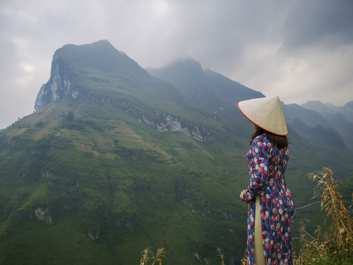 Side View Of Woman Wearing Asian Style Conical Hat Standing Against Mountains