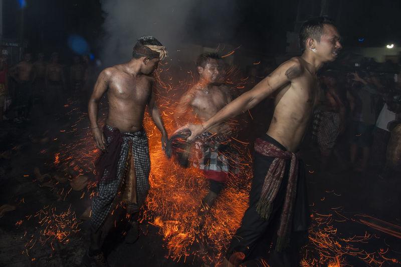 Shirtless men dancing on fire at night