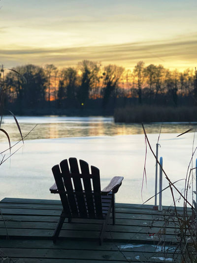 Empty chairs by lake against sky during sunset
