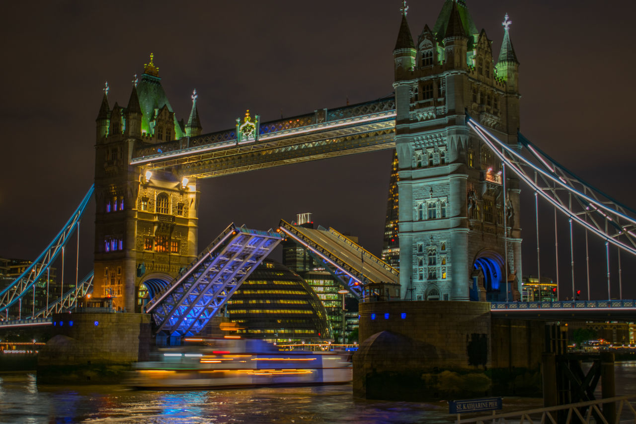 architecture, illuminated, bridge - man made structure, connection, built structure, engineering, travel destinations, night, travel, bascule bridge, transportation, tourism, river, suspension bridge, low angle view, water, chain bridge, sky, building exterior, outdoors, no people, city