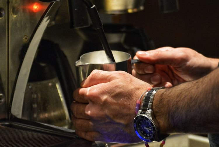 Midsection of man having coffee in kitchen