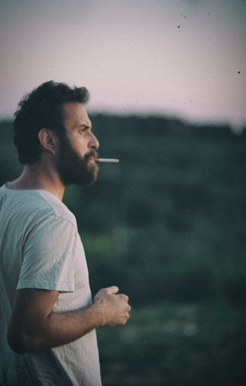 Side view of thoughtful man smoking cigarette while looking away outdoors