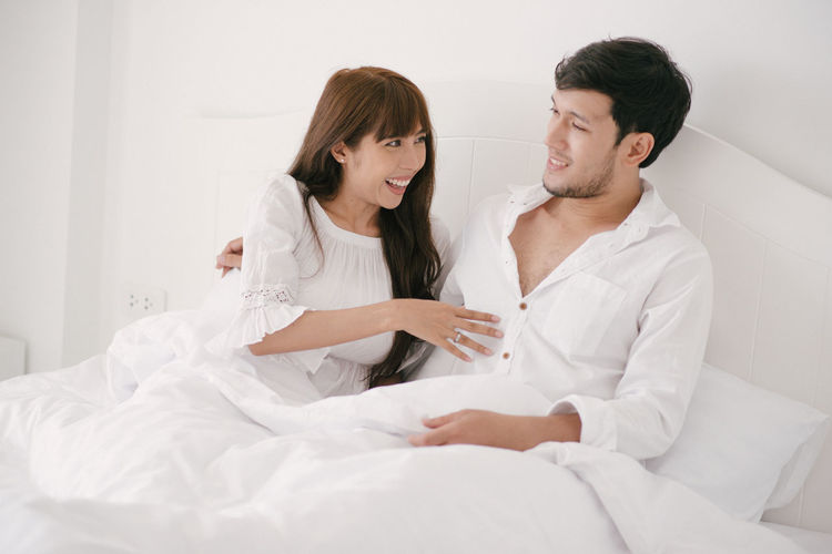 Adult Bed Bedroom Boyfriend Couple - Relationship Domestic Room Emotion Furniture Girlfriend Happiness Heterosexual Couple Indoors  Love Positive Emotion Smiling Togetherness Two People Wife Women Young Adult Young Couple Young Men Young Women