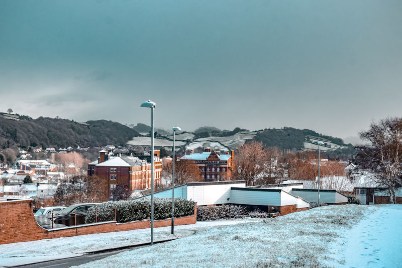 Buildings in snow covered city against sky