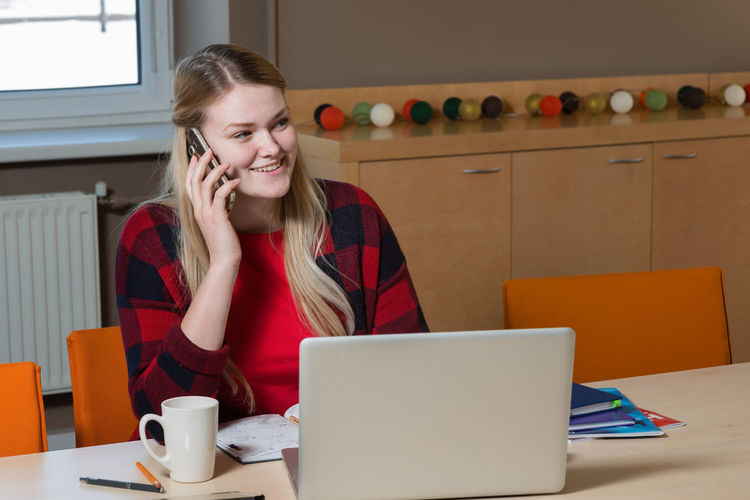 Smiling Young Woman With Laptop Using Phone On Desk