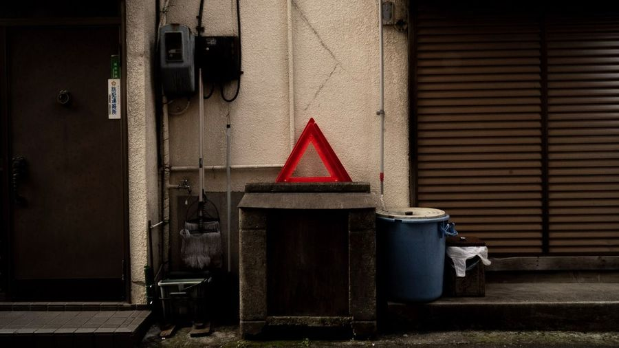 △ Warking Around City No One Cares No Peaple Signboard Red Architecture Building Exterior Built Structure Closed Shutter Door Closing