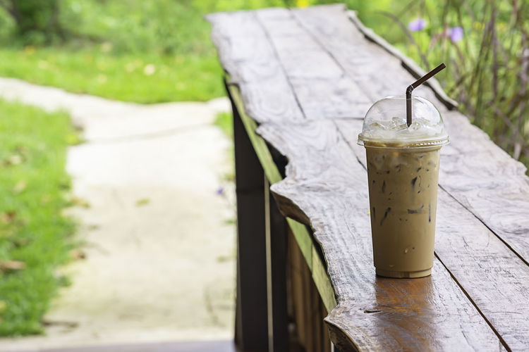 Iced coffee in glass on the table Background Pennisetum pedicellatum and pond. Bar Beautiful Beauty Beverage Blossom Bright Brown Cafe Caffeine Cappuccino Chocolate Cocoa Coffee Color Colorful Cool Cup Delicious Drink Environment Floral Flower Foliage Grass Green Ice Latte Leaf Meadow Milk Natural Nature Orange Outdoor Pennisetum Plastic Poaceae Put Refreshment Rural Straw Sugar Summer Sweet Tree Water Wildlife Wood Wooden Yellow