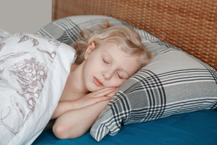 Child girl sleeping on pillow in bed at home. sweet dreams and bed vibes. everyday routine morning