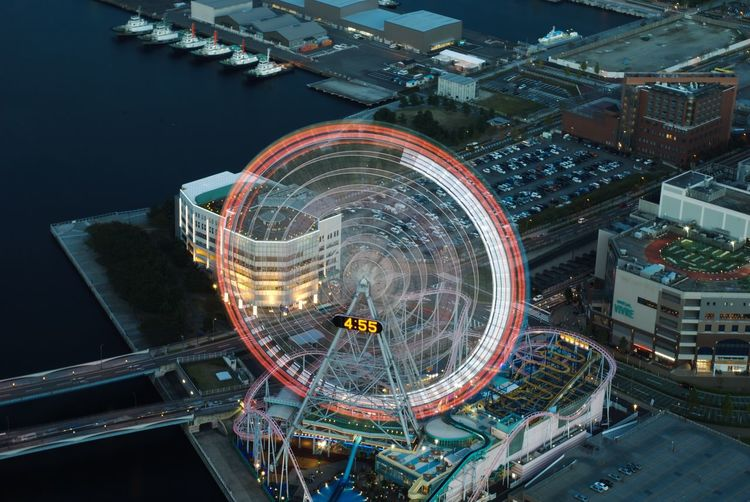 High angle view of illuminated ferris wheel in city