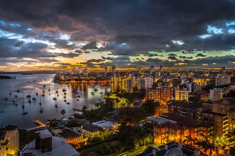 High Angle View Of Buildings And Sea Against Sky At Sunset