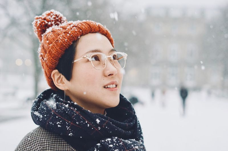 Woman Looking Away In City During Snowfall