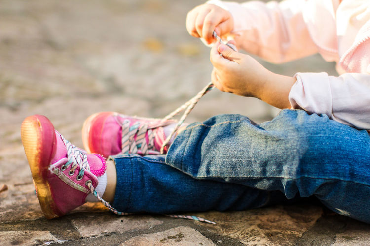 Low section of girl tying shoelace while sitting on footpath