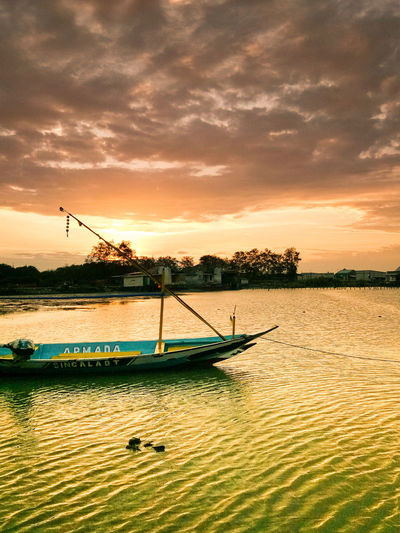 Boat sailing in river against sky during sunset